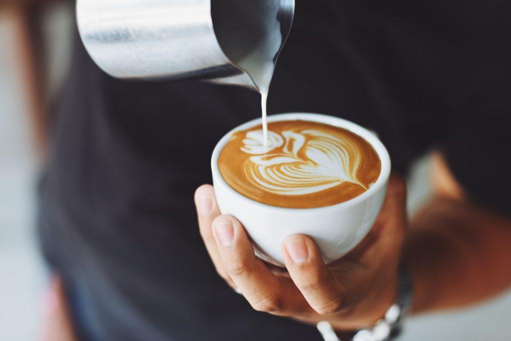 אדם מחזיק ביד אחת ספל קפה וביד השניה מוזג חלב מוקצף כדי לצייר ציור על הקפה